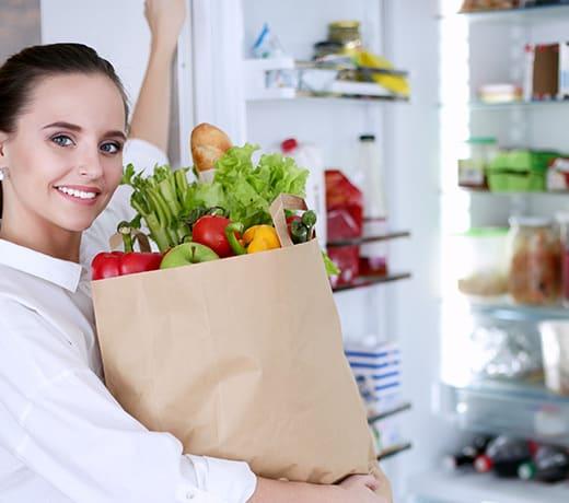 aide pour les courses : une madame ouvre le frigo